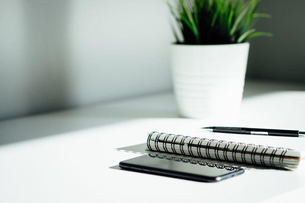 A phone next to an open notebook on a white desk