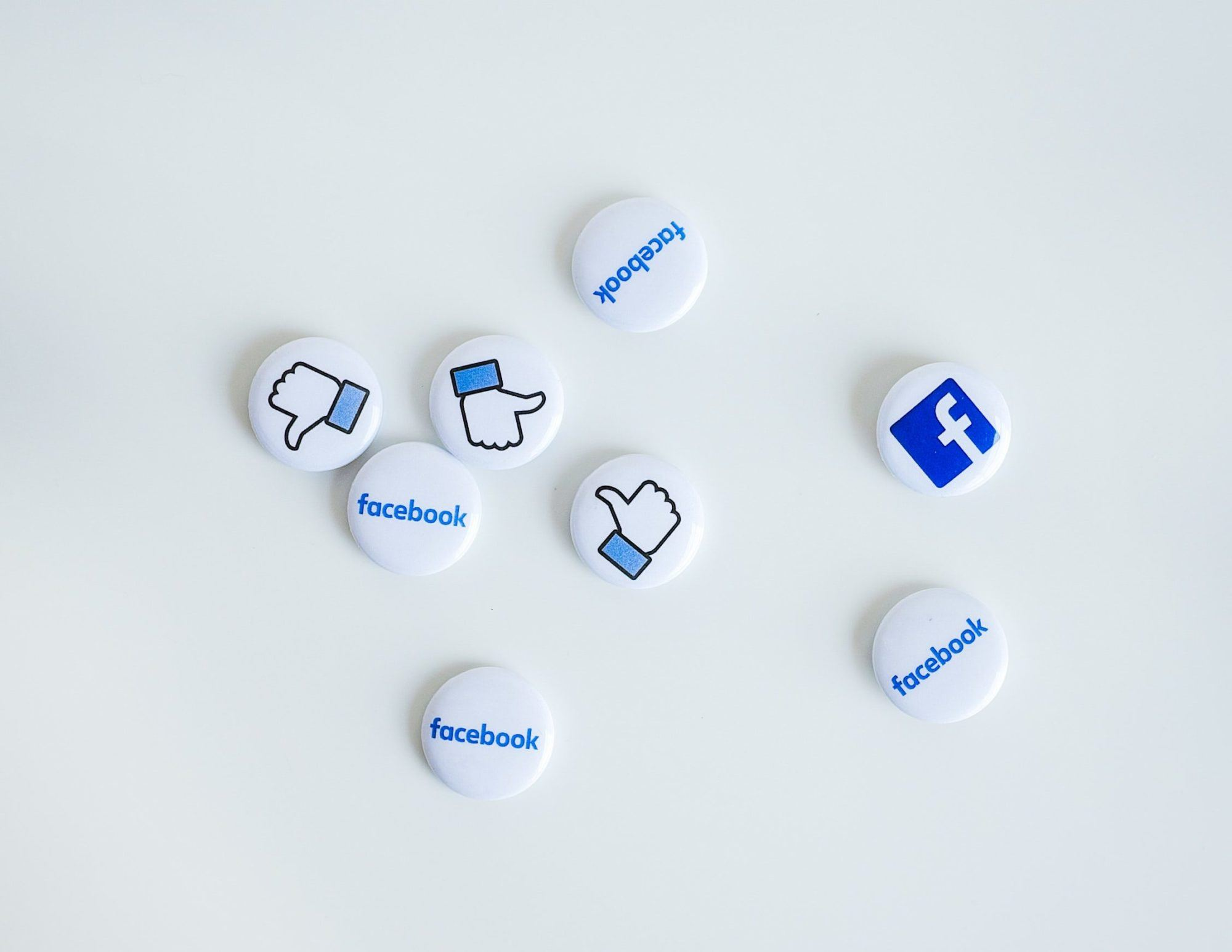 social media icon pins on a white table